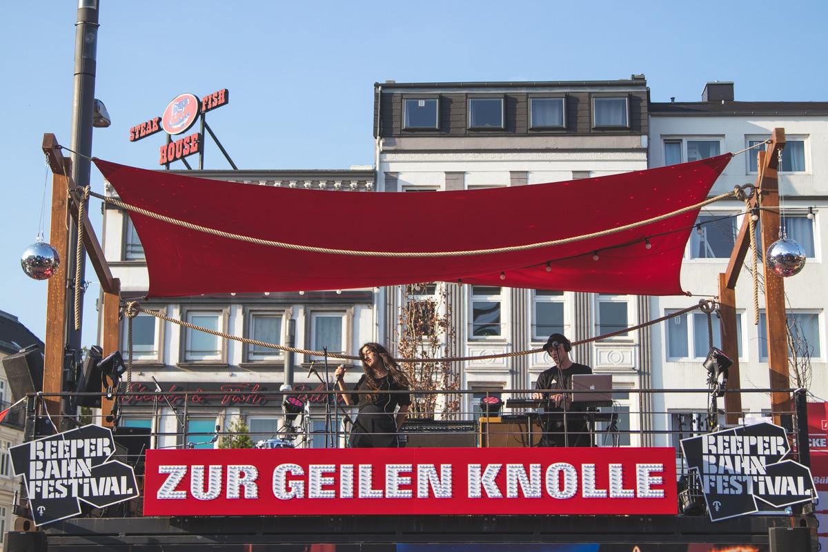 """Auch ohne ein Ticket gibt es Festivalatmosphäre auf dem Spielbudenplatz. Hier performen MADANII auf der Astra Bühne """"Zur geilen Knolle""""."""